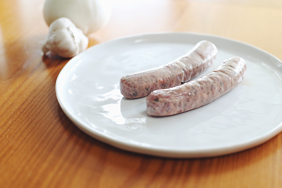 Raw sausage on plate for preparation